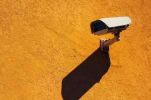 video surveillance camera mounted to orange wall