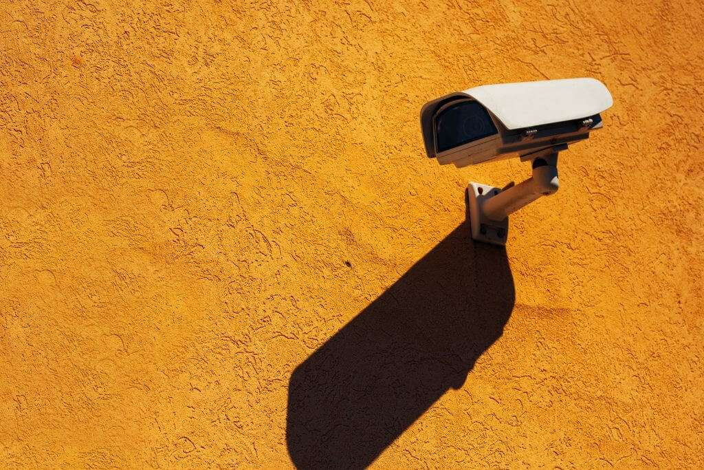 video surveillance camera mounted to orange wall