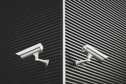two-white-cctv-cameras-on-grey-slat-walls-across-corner
