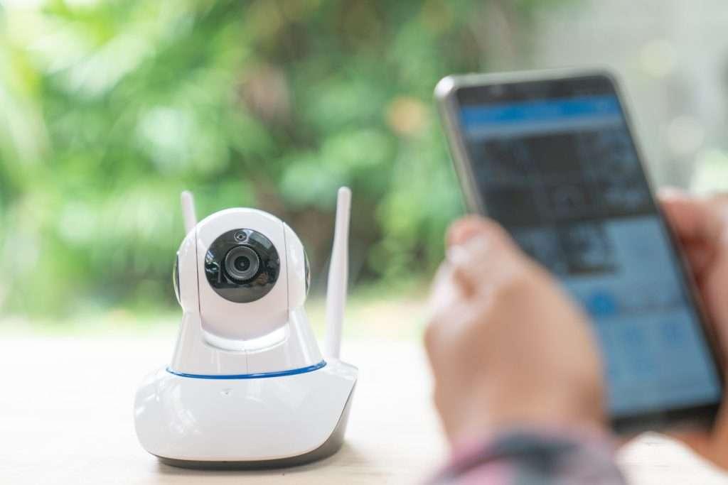 360-degree-security-cameras-on-table-with-person-s-hands-holding-tablet-displaying-surveillance-footage
