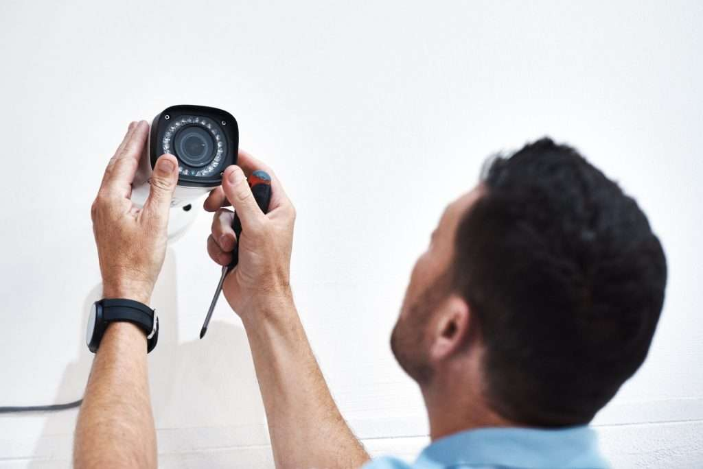 A man installing a security camera for a small business