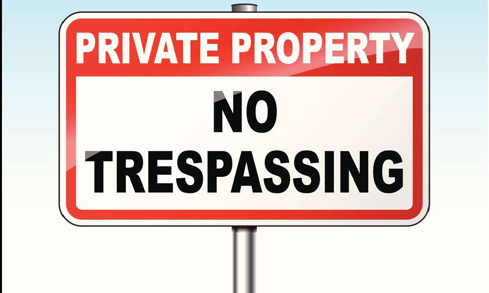 """A red and white warning sign reads """"PRIVATE PROPERTY NO TRESPASSING,"""" illustrating the signage required in many states' trespassing laws."""