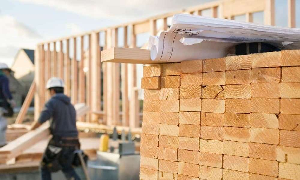 A residential construction site worker turns his back on a valuable pile of lumber